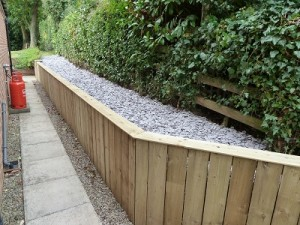 New facia wall on raised bed made with fencing materials and plum slate to cover